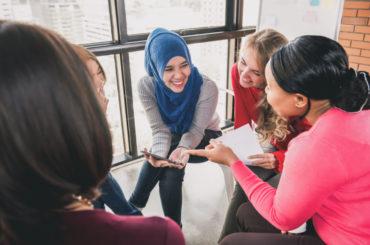 Diverse,Women,Sitting,In,Circle,Enjoying,Sharing,Stories,In,Group